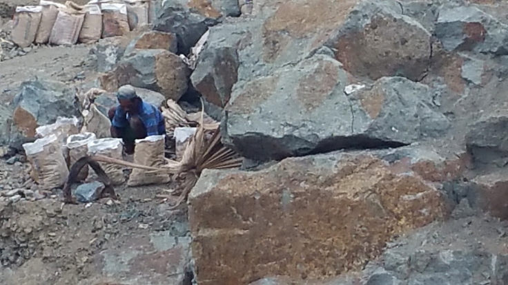 Some of the poor in Labuan Bajo, breaking rocks to sell bags of stones for building