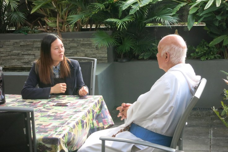 13. Emilie Ng interviewing Father for the People feature in the Catholic Leader