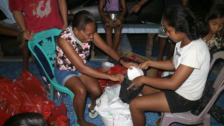 1-preparing-food-parcels-for-the-saburai-community-adding-sugar